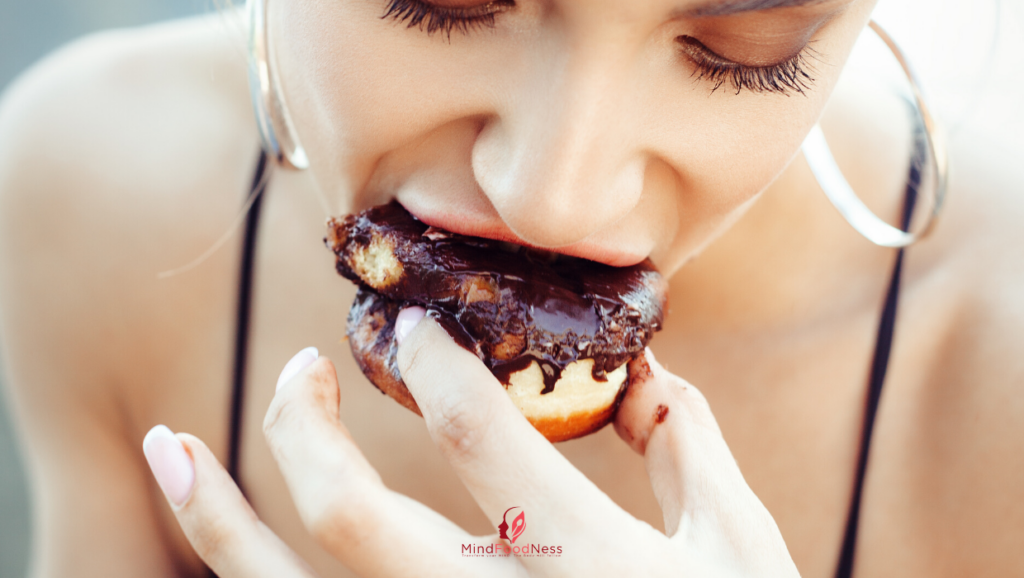 women eating a chocolate donut - how to stop binge eating and overeating