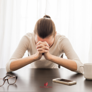 women at her desk with her head in her hands looking stressed